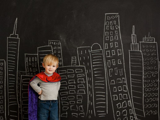 Cute toddler boy (2-3) standing against blackboard with city skyline drawn on it